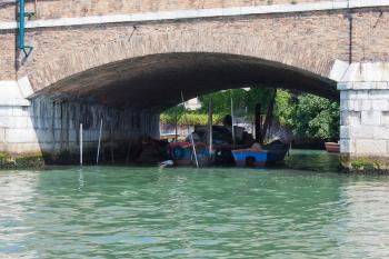 Boats moored under bridge