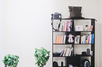 Books and Speakers on Black Wooden Shelf