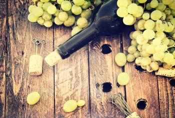 Bottle of wine with grape and corks on wooden table - Rustic looks