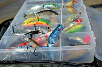 Box with lures lies on the fishing bag