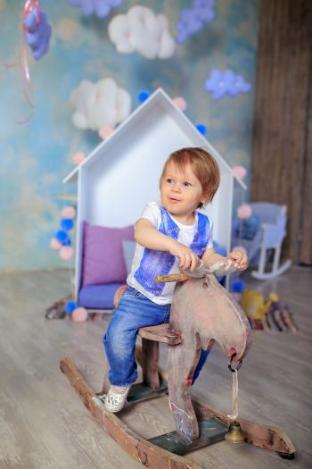Boy in Blue and White Crew Neck T Shirt Riding on Wooden Rocking Moose