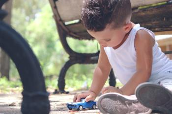 Boy in White Tank Top Playing Blue Coupe Die Cast Near Brown Wooden Bench Chair during Daytime
