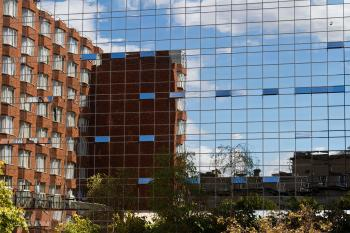 Brick Building in Glass Building Reflection