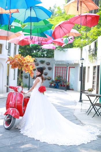 Bride posing with red scooter