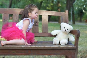 Brown Haired Girl Wearing Pink Tutu Dress Near White Bear Plush Toy
