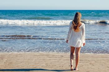 Brown Haired Woman in White Lace Long Sleeve Mini Dress Standing on Seashore