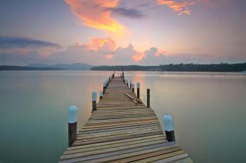 Brown Wooden Footbridge on Body of Water during Sunrise