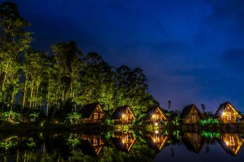 Brown Wooden House Near Body of Water during Night Time