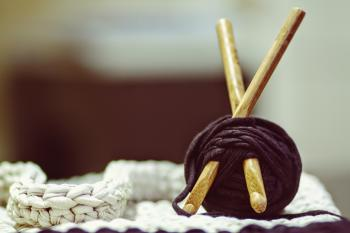 Brown Wooden Rod and Purple Yarn Ball Beside White Braided Cloth