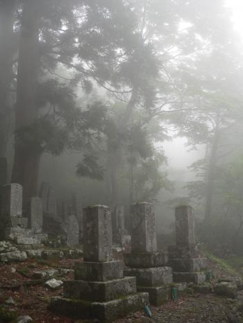 Buddhist gravestones in the mist at a mountain temple