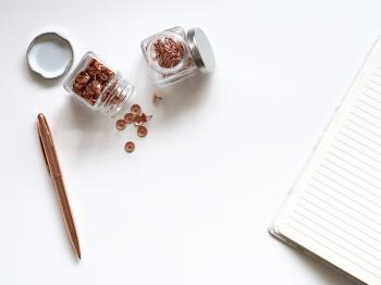 Bunch of Thumbtacks With Two Clear Glass Containers on White Surface