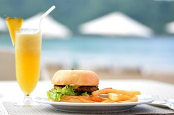 Burger With Lettuce and Fries on Plate Beside Pineapple Juice