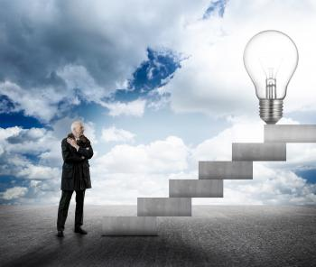 Businessman facing stairs with lightbulb