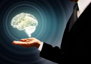 Businessman holding a brain in the palm - Skills concept - Concentric