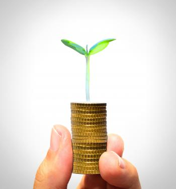 Businessman holding plant sprouting from a handful of golden coins
