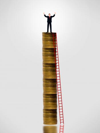Businessman on top of gold coin stack