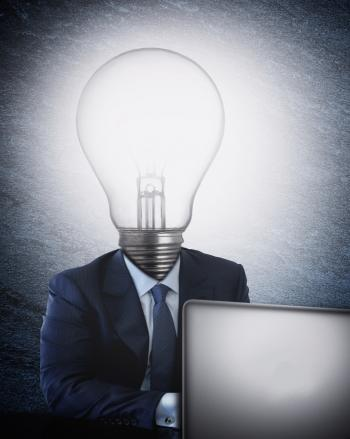 Businessman with lightbulb head in front of the computer