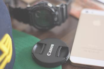 Canon Lens Cover Beside Gold Iphone 5s and Casio G Shock Chronograph Watch