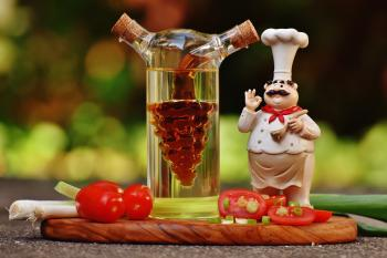 Chef Figurine Beside Clear Glass Bottle and Tomatoes