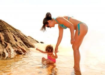 Child bathing in a natural sea pool with the help of her mother