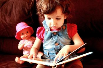 Child reading a book with doll