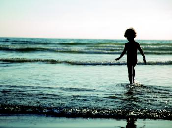 Child Walking on Seashore during Daytime
