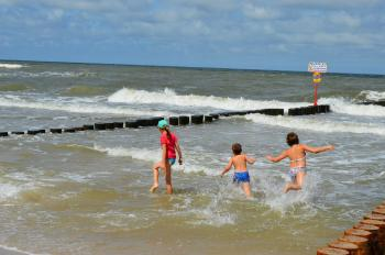 Children playing in a stormy sea near the breakwater. Baltic Sea