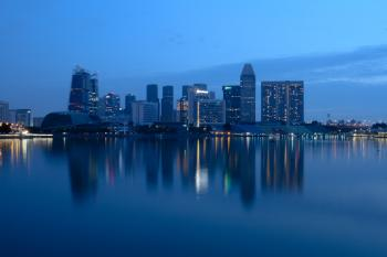 City Buildings Beside Body Of Water During Night Time