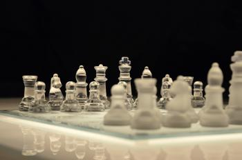 Clear Glass and White Chess Piece on White Chess Board With Black Background