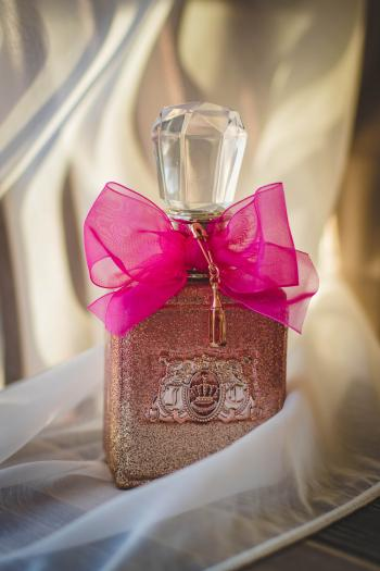 Close Photograph of Glitter Pink Fragrance Bottle With Red Ribbon