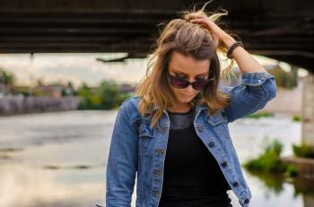 Close Up Photo of Woman Wearing Black Top and Blue Denim Button-up Jacket