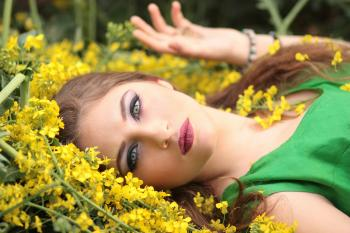 Close-up Portrait of Young Woman With Yellow Flowers