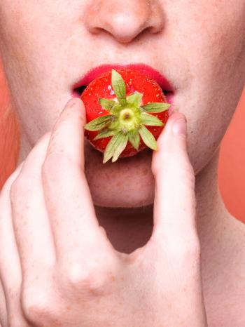 Close up woman mouth eating strawberry