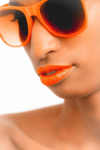 Closeup and Selective Focus Photograph of Woman Wearing Orange-framed Wayfarer-style Sunglasses