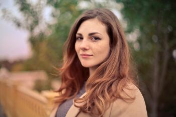 Closeup Photo of Woman With Brown Coat and Gray Top