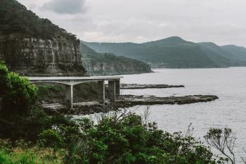 Concrete Bridge Near Mountain Above Shoreline Under Cloudy Sky