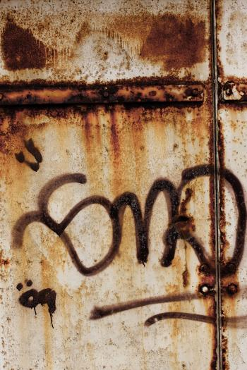 Corroded Metal Fence with Graffiti