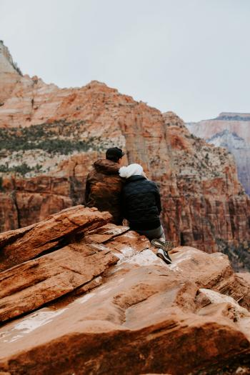 Couple Sitting on Rock Cliff