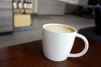 Cup of hot coffee in Starbucks with logo on the cup