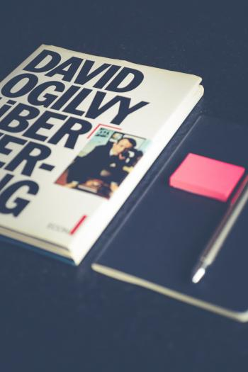 David Ogilvy Book Lying Beside Black Leather Booklet