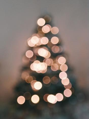 Defocused Image of Illuminated Christmas Tree Against Sky