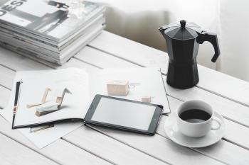 Digital tablet with cup of coffee on a white desk