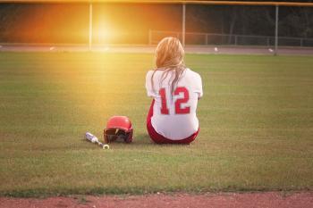 Female Baseball Player Sitting on Grass Field Beside Helmet and Baseball Bat