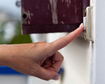 Finger pressing a doorbell