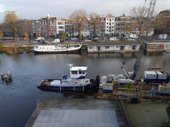floating crane in the canal with other construction boats, Amsterdam