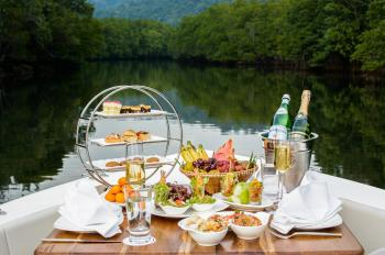 Food Photography of Food and Wine Bottles on Table Inside Boat