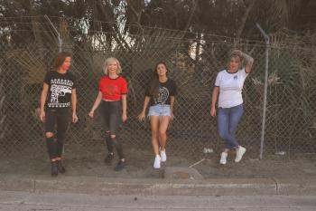 Four Women Standing Against Wire Fence