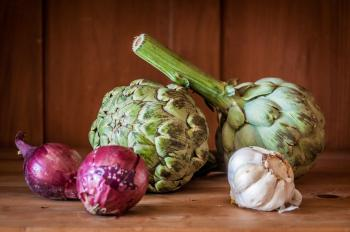 Fresh artichokes on rustic wood