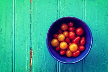 Fresh colorful cherry tomatoes on wood background - Organic farming