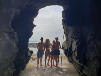 Friends posing in the hole in the mountain on the beach